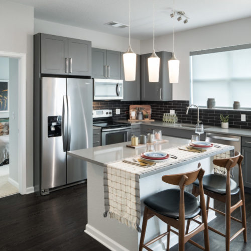 gourmet kitchen with stainless steel appliances and pendant lighting - Live Effortlessly in Comfort